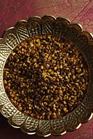 Indian digestive mukhwa seeds on brass dish on pink sari cloth closeup - Asia Images Group