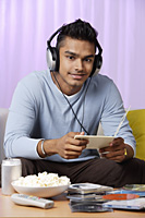 young man listening to music with headphones on - Asia Images Group