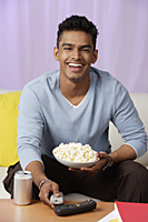 young man holding popcorn in hand, laughing - Asia Images Group