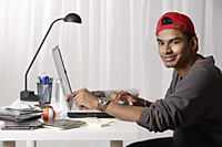 young man with red cap working on laptop - Asia Images Group