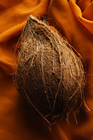 coconut with shell on top of draped cloth - Asia Images Group