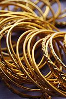gold Indian bangles on purple sari cloth closeup - Asia Images Group
