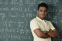 young man standing proudly in front of chalkboard - Asia Images Group