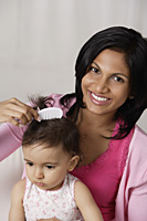 woman combing baby's hair - Asia Images Group
