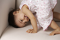 toddler playing on the couch - Asia Images Group