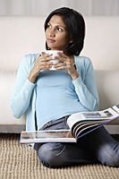 woman holding a mug, book on her lap - Asia Images Group