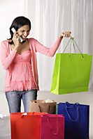 woman on the phone and holding green shopping bag - Asia Images Group