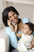 woman talking on mobile phone, baby on her lap - Asia Images Group