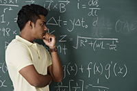 young man standing in front of chalkboard, thinking - Asia Images Group