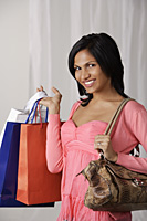 woman in pink blouse holding shopping bags - Asia Images Group
