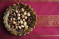 Mix of Indian beans, seeds and nuts in brass dish on pink sari cloth - Asia Images Group