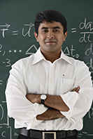 teacher standing in front of chalkboard, arms crossed - Asia Images Group
