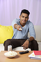 young man with television remote - Asia Images Group
