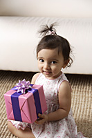 toddler holding a present - Asia Images Group