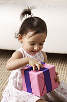 toddler girl opening present - Asia Images Group