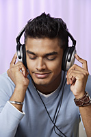 young man with headphones on, listening to music intently - Asia Images Group
