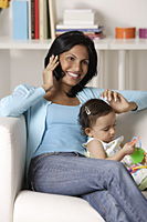 woman talking on mobile phone, sitting with baby - Asia Images Group