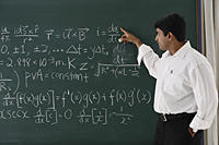 teacher explaining formula at chalkboard - Asia Images Group