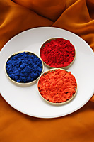 red, blue and orange Indian powder paints - Asia Images Group