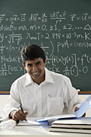 teacher sitting at desk - Asia Images Group