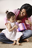 woman with baby, opening her present - Asia Images Group