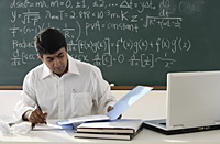 teacher sitting at desk, working - Asia Images Group
