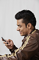 side profile of young man in jacket, using mobile phone - Asia Images Group