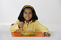 Girl eating briyani rice - Asia Images Group