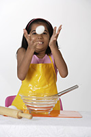 Girl baking, tossing egg - Asia Images Group