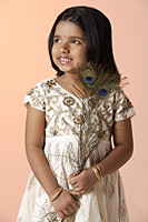 Little girl wearing traditional Indian clothing holding peacock feathers - Asia Images Group