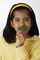Girl smelling green leaf - Asia Images Group