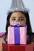 Little girl holding birthday presents - Asia Images Group