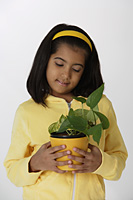 Girl holding plant - Asia Images Group