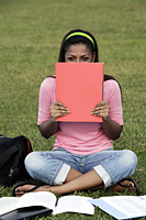 young woman laughing behind folder - Asia Images Group