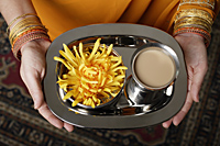 tight shot of woman holding a tray with tea. - Asia Images Group