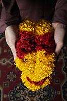 Hands holding flower garlands. - Asia Images Group