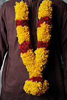 Man wearing flower garlands. - Asia Images Group