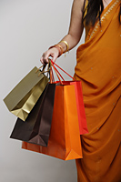 Woman wearing sari holding shopping bags - Asia Images Group