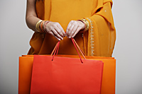crop shot of woman in sari holding shopping bags - Asia Images Group