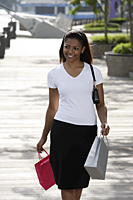woman walking outside holding shopping bags - Asia Images Group