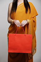 Cropped shot of woman wearing sari holding orange shopping bag - Asia Images Group