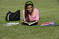 young woman laying on grass studying - Asia Images Group