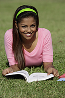 young woman laying on grass reading a book - Asia Images Group
