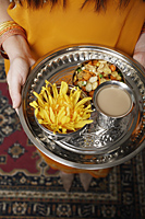 tight shot of a woman holding a tray of tea and snacks - Asia Images Group