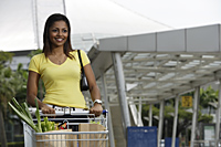 woman pushing shopping cart outside of store - Asia Images Group