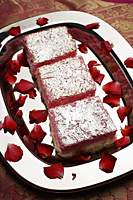 Indian pink sweets on silver tray with rose petals - Asia Images Group