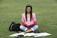 young woman sitting on the grass studying - Asia Images Group