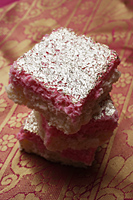 A stack of Indian pink sweets with silver topping. - Asia Images Group