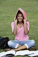 Young woman covering her head with a folder - Asia Images Group