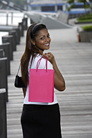 woman walking outside holding shopping bag and smiling - Asia Images Group